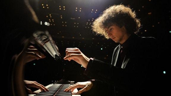 Junger Mann mit lockigen Haaren sitzt und spielt am Flügel oder Klavier, Perspektive auf Höhe Klaviertasten, Gegenlicht von Bühnenbeleuchtung
