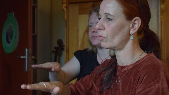 Zwei Frauen singen und machen dazu Handbewegungen: Susanne Haupt und Andrea Schmetzstorff.