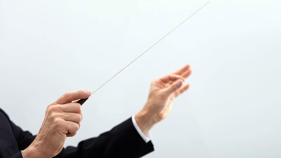 Person, die mit Dirigentenstab dirigiert