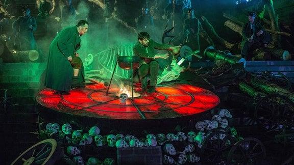 Zwei Personen mit langen Gewändern in einem grün-roten mystischen Bühnenbild, in der Mitte ein Dreibein-Kochtopf über Feuer, Totenköpfe und Skelette