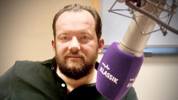 Porträt von Andris Nelsons im MDR KLASSIK-Studio am MDR KLASSIK-Mikrofon: Mann mit dunkleren Haaren und Bart sowie schwarzem, leicht aufgeknöpftem Hemd und neutralem Blick in die Kamera.