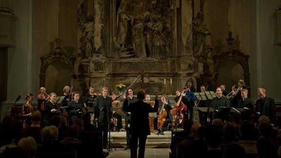 Das Ensemble Cappella Sagittariana Dresden auf einem Kirchenalter, Blick auf das hohe Bauwerk, unten das Ensemble