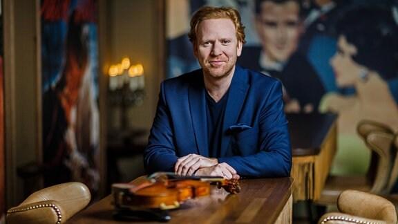 Mann mit blond-roten Haaren, Drei-Tage-Bart und blauem Sakko sitzt an einem Holztisch, vor ihm tiefenunscharf eine Violine, hinter ihm eine Unscharfe Bildtapete, Sessel und Kerzenständer, dunkle, cineastische Farben