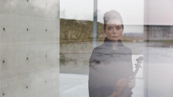 Frau mit hochgesteckten, dunklen Haaren spiegel sich in einer Glasfläche, in der Hand eine Geige, an der Seite Betonwand, im Hintergrund gespiegelte Landschaft