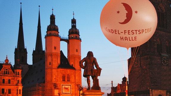 Abendstimmung am Marktplatz von Halle, Marktkirche mit vier Türneb rot angestrahlt, davor Händel-Statue mit Rücken nach vorn, ganz im Vordergrund Luftballon mit Logo der Händel-Festspiele.