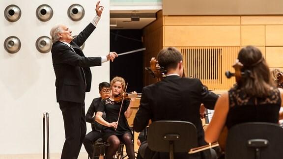 Aufnahme von der Seite: Dirigent Heribert Beissel (älterer Mann mit Anzug und Taktstock, gehobenem Arm mit Daumen und Zeigefinger zusammen, Augen geschlossen) steht vor Musikern des Jugendsinfonieorchesters Sachsen-Anhalt, die teilweise mit dem Rücken zum Fotografen sitzen.