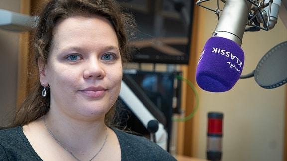 Portrait von Julia Nagel (junge Frau mit langen braunen Haaren sitzt im MDR-Studio neben einem Mikrofon)