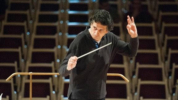 Michael Sanderling (Dirigent), Mann mit schwarzen, lockigen Haaren und schwarzer Kleidung steht auf einem Podest vor leeren Stuhlreihen, hebt Takstock und linke Hand
