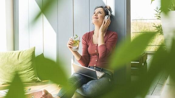 Ene Frau hört mit Kopfhörern Musik, in der Hand ein gesundes Getränk, im Vordergrund unscharfe grüne Blätter
