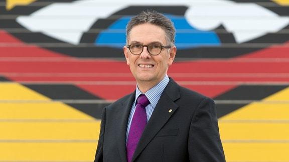 Halbnahes Porträt von Oliver Zille, dem Chef der Leipziger Buchmesse: Mann mit Anzug und runder Brille vor bildfüllender, leicht unscharfter, farbig gestalteter Treppe mit Buchmesselogo im Hintergrund