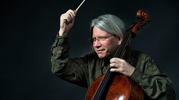 Mann mit kinnlangen grauen Haaren und Brille sitzt vor schwarzem Hintergrund am Cello, hebt den Bogen, blickt zur Seite, Auschnitt bis zur Hüfte