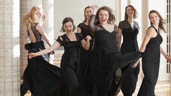 Das Ensemble Sjaella in einem Gang. Junge Frauen mit schwarzem, langen Kleid, dynamisch (springend, drehend)