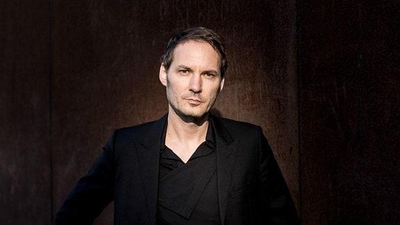 Halbnahes Porträt von einem Mann vor schwarzem Hintergrund, Gesicht erleuchtet von Mann ohne Bart mit kürzeren, dunklen Haaren