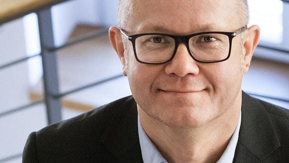 Foto von schräg oben auf Mann mitsehr kurzen Haaren (bis keine Haare), schwarzer Brille, Hemd, Sakki und freundlichem Blick. Im Hintergrund unscharf ein Treppenhaus.