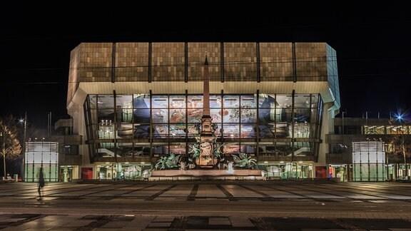 Gewandhaus im Dunkeln, Frontalansicht: Beleuchtetes Konzertgebäude mit großer, frontaler Glasfäche, im inneren großes beleuchtetes Wandgemälde. Im Vordergrund: Mendebrunnen, auch beleuchtet, auf dem Augustusplatz.
