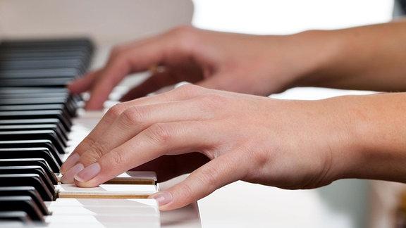 Hände auf Klavier beim Spiel.