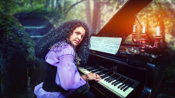 Frau mit schwarzen, gelockten Haaren und mytisch-gruseligem Blick über Schulter an einem Klavier mit schwarzem Kerzenleuchter, im Hintergrund unscharf Wald