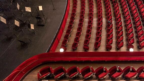 Leere Stühle in Konzertsaal sowie Notenständer auf der Bühne ohne Musiker, Ansicht von oben.