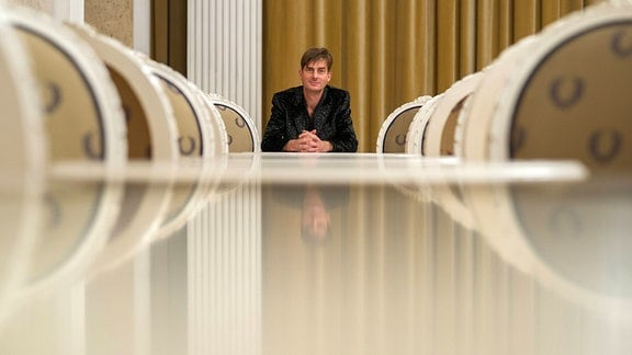 Komponist Ludger Vollmer sitzt am Ende eines langen Tisches und schaut zur Kamera.