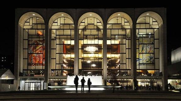 Metropolitan Opera in New York am Abend: Gebäude mit fünf hohen, nach oben runden Fenstern. Beleuchtet, Blick nach innen, u.a. Wandgemälde, Vordergrund: Springbrunnen und Silhouette von Menschen