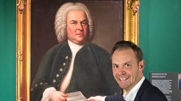 Mann im Anzug vor Gemälde von Johann Sebastian Bach.