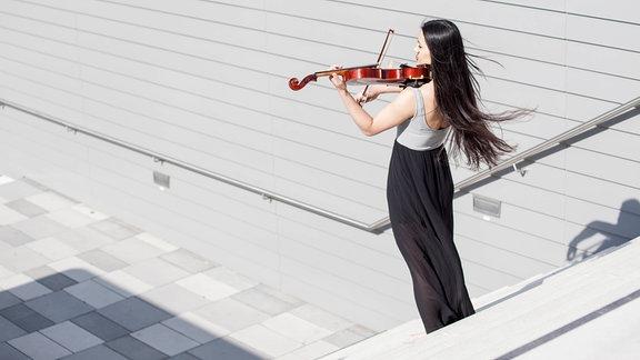 Eine Frau spielt Violine auf einer Treppe.