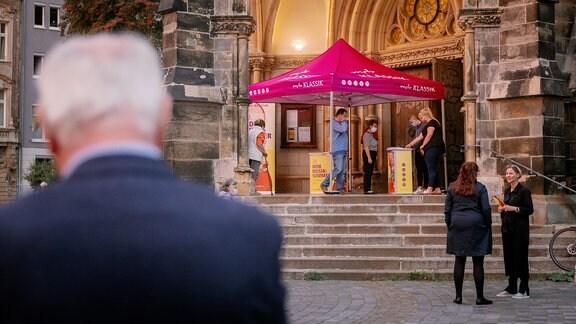 """Aufnahme des Haupteingangs einer Kirche. Davor steht ein Pavillion mit Aufschrift """"MDR"""""""