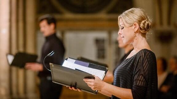Sängerin und Sänger eines Chores mit Mappen.