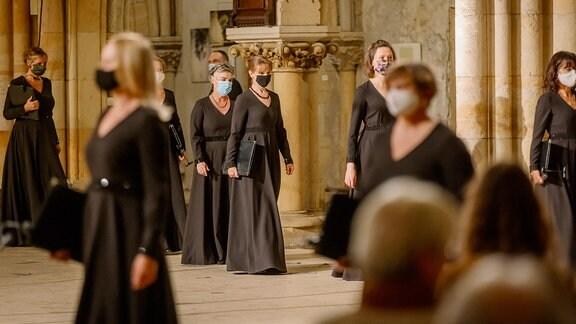 Sängerinnen eines Chores betreten mit Mundschutz die Bühne in einer Kirche.