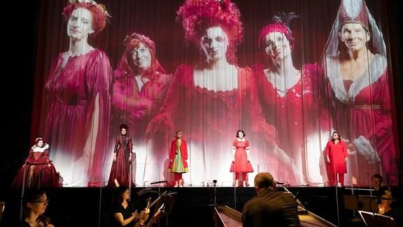 """Aufnahme einer Bühne auf der drei Schauspielerinnen stehen. Sie werden auch auf die Bühnenwand projiziert. Zitattafel mit der Aufschrift: """"Georg D. Händel feierte an der Oper Halle Premiere""""."""