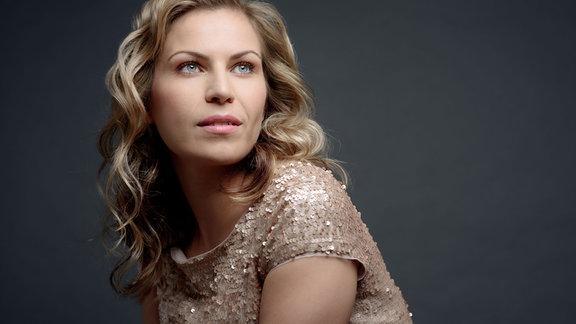Porträt Frau von der Seite mit langen, gewellten, blonden Haaren, blickt zur Seite Richtung Kamera, aber nach oben