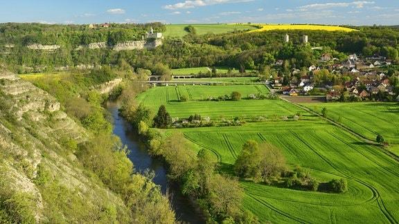 Flusslandschaft Saale von oben, links hügelig, rechts grüne Felder und Dorf, Hügel und Rapsfeld im Hintergrund