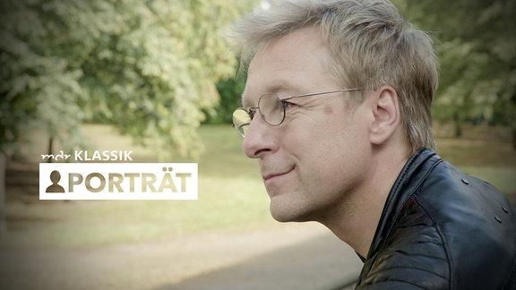 """Seitliches Porträt von Mann mit blonden Haaren, ohne Bart, drahtige Brille und Lederjacke lehnt auf Geländer und schaut in grünen Park (unscharf im Hintergrund). Logo """"MDR KLASSIK-Porträt"""""""
