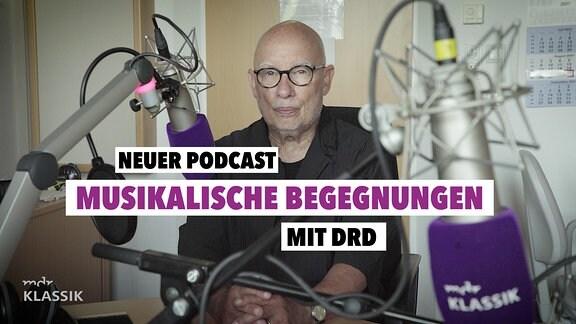 """Mann mit kahlem Kopf und schwarzer, runder Brille in einem Studio mit Mikrofonen mit MDR KLASSIK-Logo. Text auf Bild: """"Neuer Podcast: Musikalische Begegnungen mit DRD"""""""
