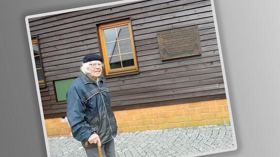 Ein stilisiertes Foto mit weißem Rahmen liegt schräg. Darauf Werner Wolf vor einem Holzhaus mit Gedenktafel. Älterer Mann mit weißem, längeren Haar, Brille, Baskenmütze, Regenjacke und Stock, freundlich in die Kamera blickend.