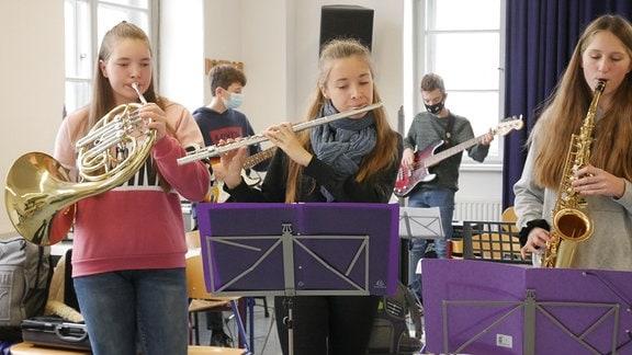 Jugendliche spielen auf Instrumenten bei einer Ensembleprobe.