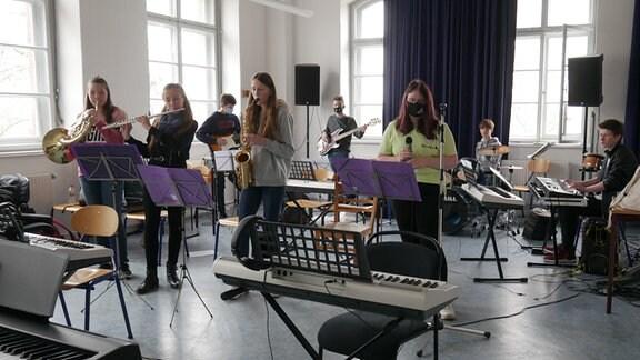 Jugendliche spielen auf ihren Instrumenten bei einer Ensembleprobe.
