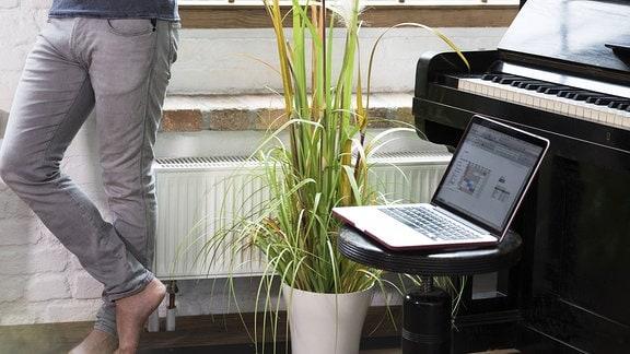 Vor einem Klavier liegt ein Laptop.