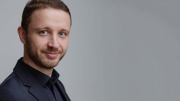 Mann mit schwarzem Hemd, Bart, ohne Brille und kurzen, dunkelblonden Haaren schaut leicht über die rechte Schulter und lächelt.