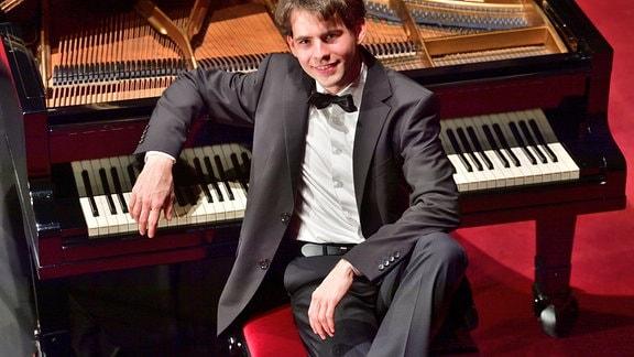 Der Organist und Pianist Markus Schmidt aus nahezu Vogelperspektive, am offenen Flügel sitzend – junger Mann mit Sakko, Hemd und Fliege