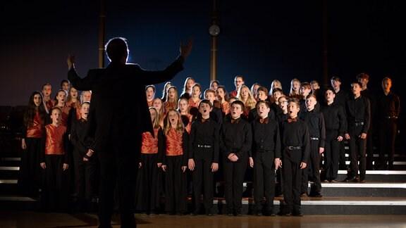 MDR-Kinderchor im Bühnenlicht, davor mit dem Rücken der Leiter Alexander Schmitt mit Konturlicht, festliche Stimmung
