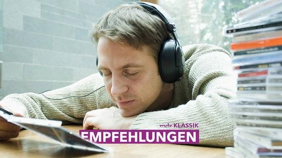 Ein Mann mit Kopfhörern lehnt auf dem Tisch neben einem CD-Stapel, in der Hand eine offene CD-Hülle.