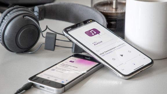 Zwei Mobiltelefone: Auf dem einen läuft ein MDR KLASSIK-Podcast, auf dem anderen die ARD Audiothek. Dahinter Kopfhörer, eine Kaffeetasse und eine French Press als Kaffeekanne.