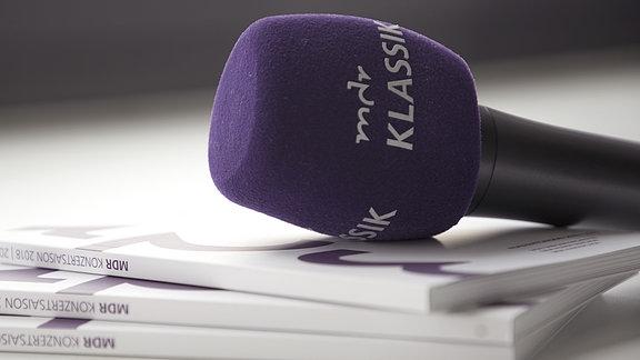 Ein Stapel Konzertbroschüren der Saison 2018/2019, dazu ein MDR-KLASSIK-Mikrofon