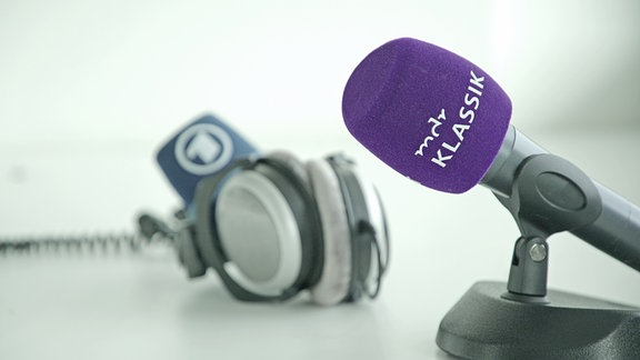 MDR KLASSIK-Mikrofon auf Ständer im Vordergrund, im Hintergrund Kopfhörer und ARD-Mikrofonschutz.