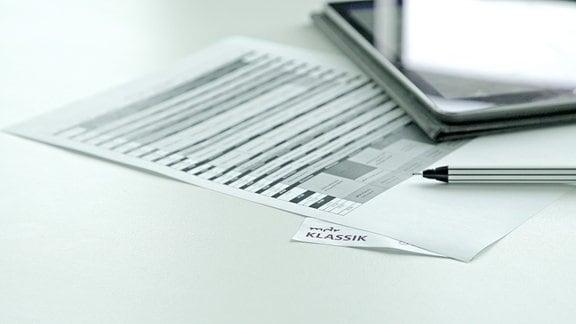 Tabelle mit Programmschema, Tabletcomputer und Stift, viel Tiefenunschärfe