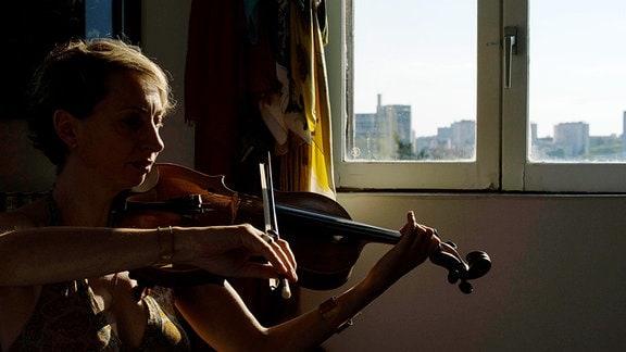 Die Bratschistin Maria Moscon aus Frankreichz sitzt daheim am Fenster und spielt ihr Instrument. Licht beleuchtet nur die Konturen sowie Licht im Fenster.