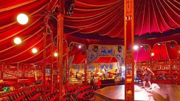 Zirkuszelt im roten Licht, innen, im Hintergrund ein Orchester bei der Probe.