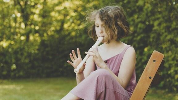 Ein Mädchen spielt Flöte im Garten