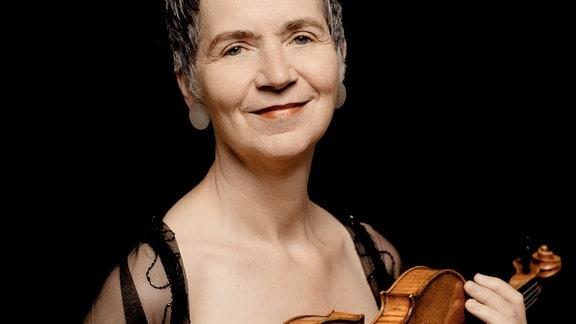 Die Geigerin Petra Müllejans, lächelnde Frau mit kurzen, dunkelgrauen Haaren -- in der Hand eine Geige